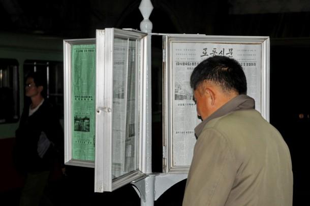 Житель Северной Кореи читает газету на станции метро